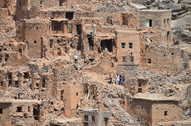Touristen klettern auf Ruinen des Saiq Plateaus.